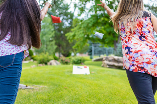 In Western Colorado Two Adult Senior Female Friends in focus in foreground with backs to camera Having Fun Together Outdoors Playing Bean Bag Toss Corn Hole Game in lush green setting with bean bag and game board blurred in background Part of Two Adult Senior Female Friends Having Fun Together Outdoors Series 4K Video Also Available for this Photo Series (Shot with Canon 5DS 50.6mp photos professionally retouched - Lightroom / Photoshop - original size 5792 x 8688 downsampled as needed for clarity and select focus used for dramatic effect)