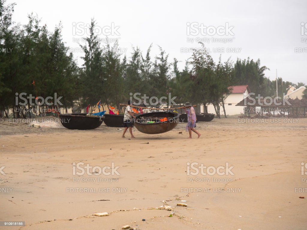 Two adult Vietnamese man in traditional clothes carry a boat against the background of the South China Sea and the cloudy sky stock photo