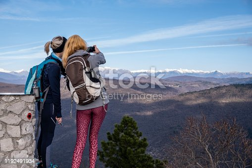 Two young adult woman hiking: border mountain of Italy and Slovenia. Europe.
