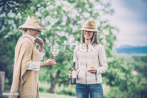 Two Adult Women having Fun Outdoors, Drinking White Wine