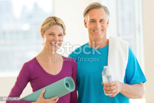 istock Two adults holding exercise related items 451253809
