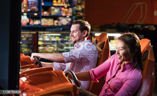 Two multi-ethnic adults playing a driving game in a video arcade. They could be competing against each other, or working together. They are both in their 30s. The focus is on the man.