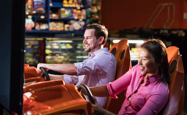 Two adults playing driving game in video arcade stock photo