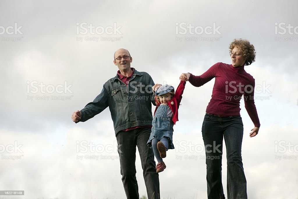 Two adults playing with little girl royalty-free stock photo