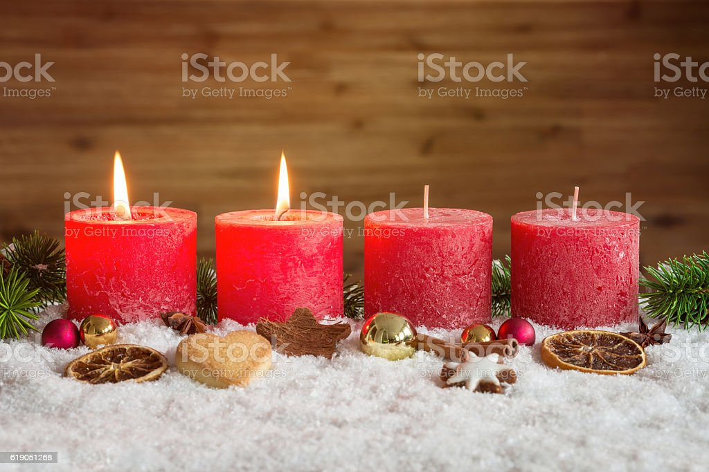 Two advent candles lit in snow stock photo