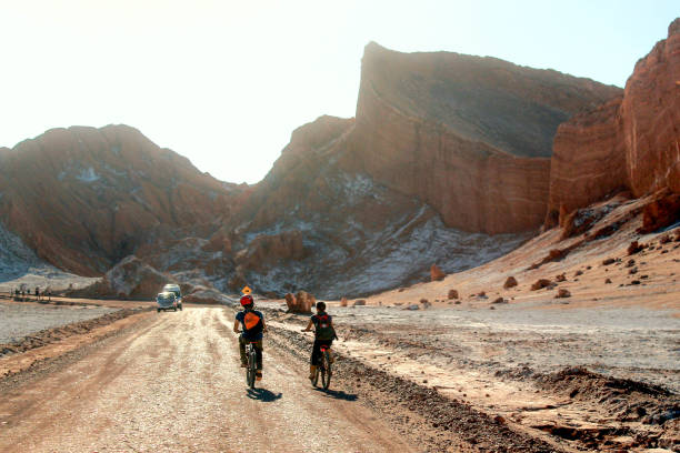 Two adventurous tourists pedal through the Atacama Desert heading for a large rocky wall, stock photo