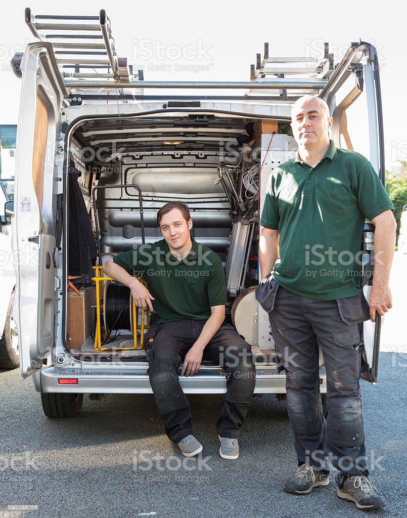 Two aerial communication engineers at back of their van. Стоковые фото Стоковая фотография