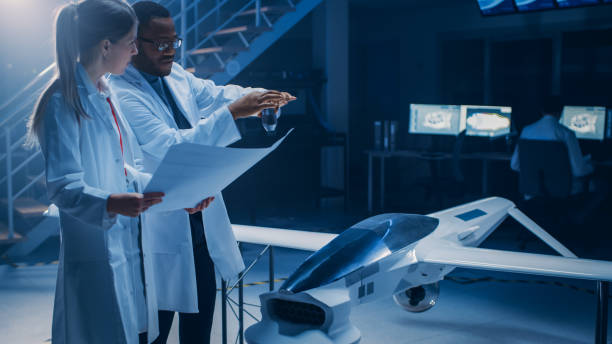 Two Aerospace Engineers Work On Unmanned Aerial Vehicle / Drone Prototype. Aviation Scientists Talking, using Blueprints. Industrial Laboratory with Commercial Aerial Surveillance Aircraft stock photo