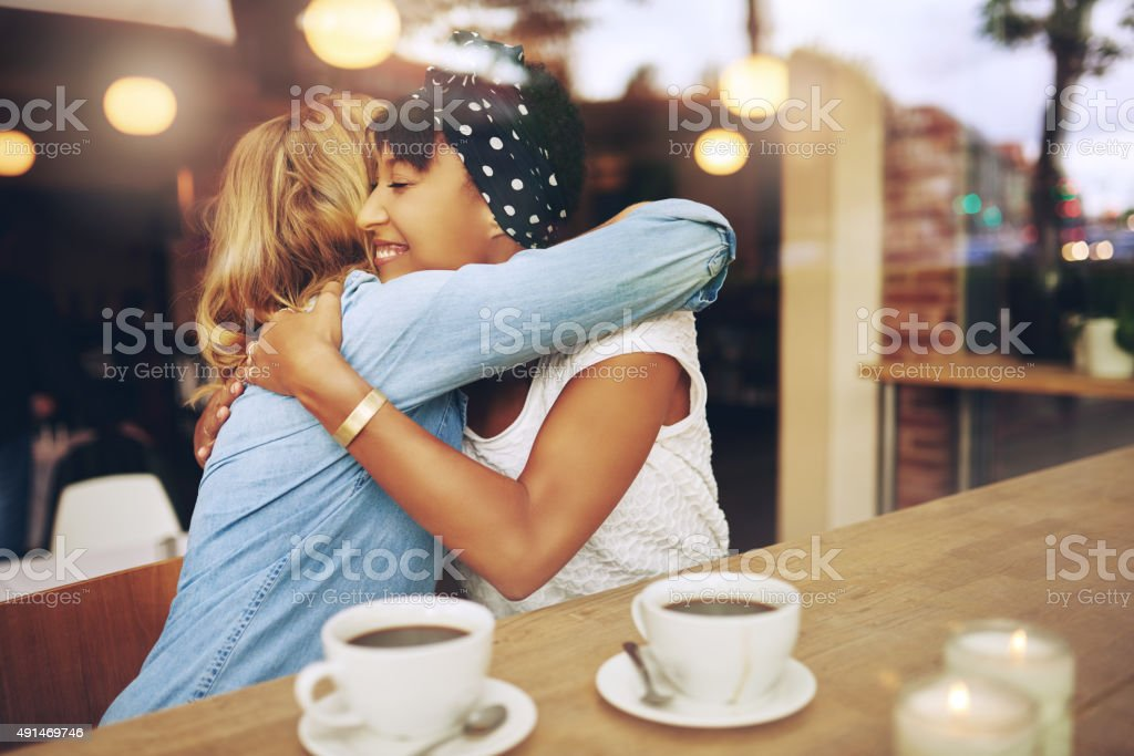 Two affectionate girl friends embracing stock photo
