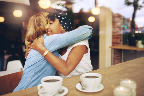two affectionate girl friends embracing - positive energy stock photos and pictures