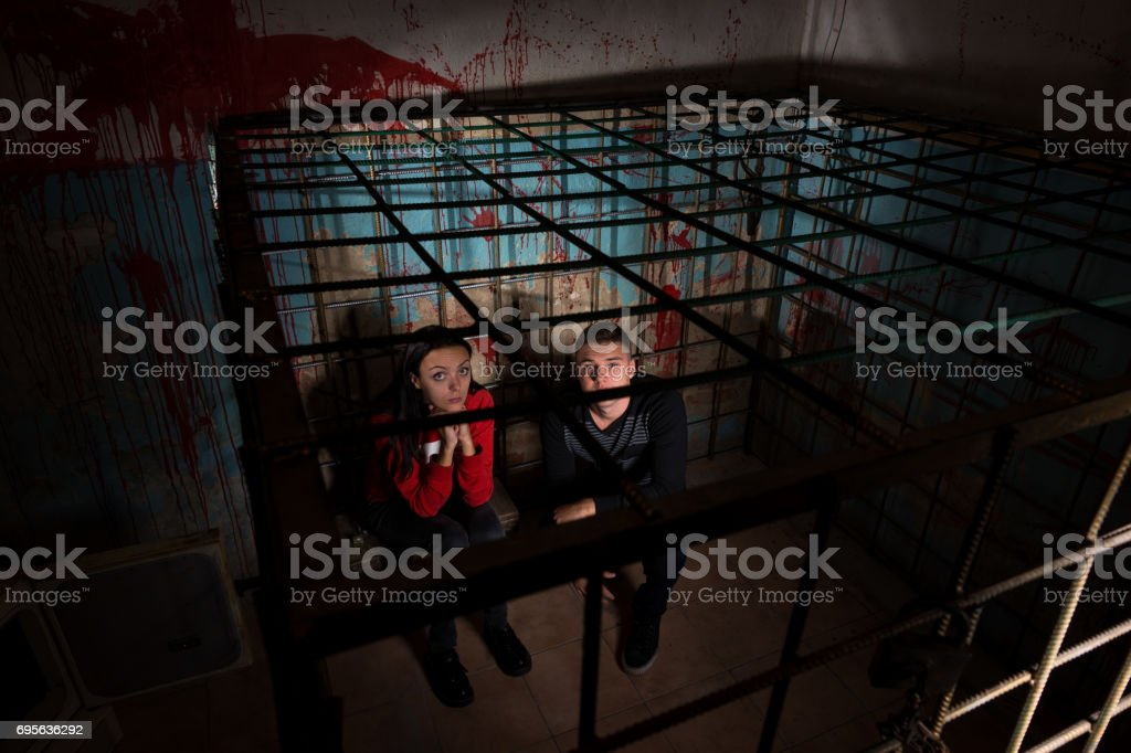Two afraid Halloween victims imprisoned in a metal cage stock photo