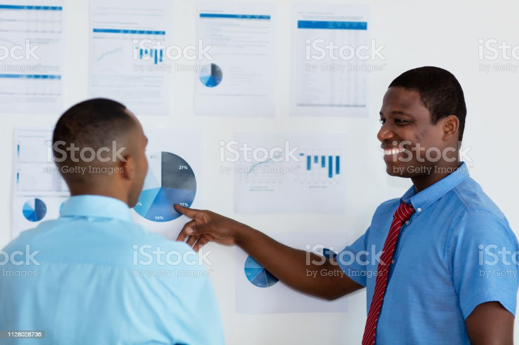 Dos hombres de negocios afroamericanos hablando de estrategia empresarial - foto de stock