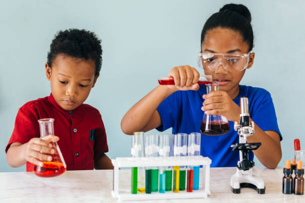 Two African American mixed kids testing chemistry lab experiment stock photo