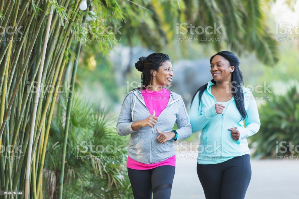Two African American women jogging together stock photo