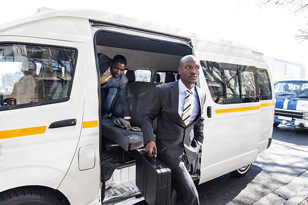 Two african businessman getting out of a taxi. stock photo