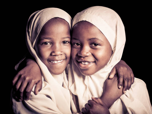 Two African Muslim Girls (Isolated on Black) stock photo