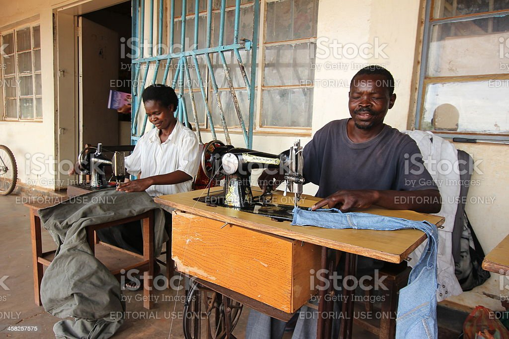 Two African tailors work on their old sewing-machines in Africa stock photo