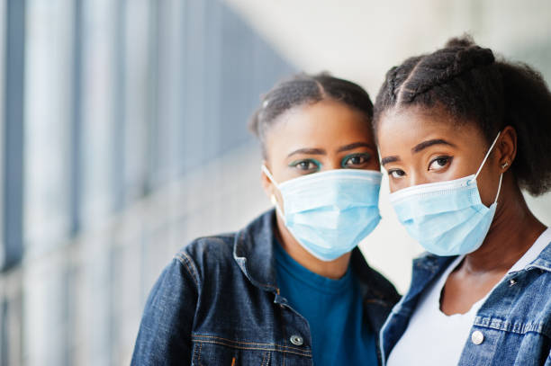 Two african woman friends in jeans jacket wearing protective masks. Virus concept health, medical. stock photo