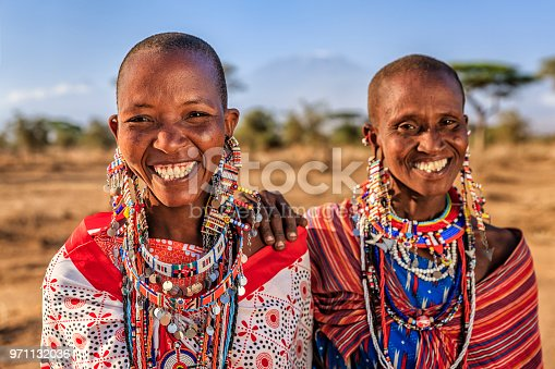 Two African woman from Maasai tribe - Mount Kilimanjaro on the background. Maasai tribe inhabiting southern Kenya and northern Tanzania, and they are related to the Samburu.