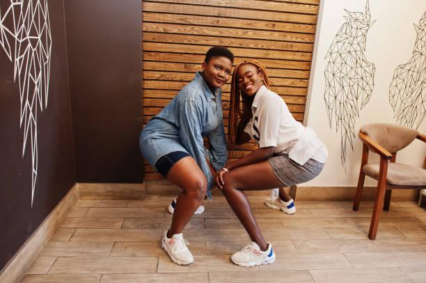 zwei afrikanische damen in stilvoller freizeitkleidung, die gegen die hölzerne wand posierten, setzten sich hin und tanzen twerk. - damen hosen angels stock-fotos und bilder