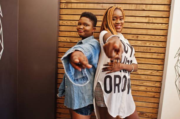 zwei afrikanische damen in stilvoller, lässiger kleidung posieren gegen die hölzerne wand und zeigen finger vor der kamera. - damen hosen angels stock-fotos und bilder