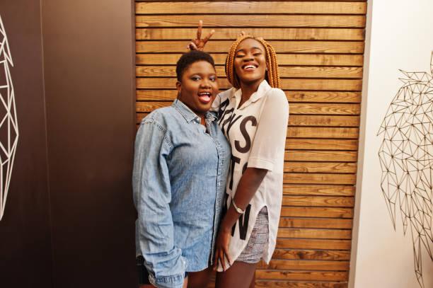 zwei afrikanische damen in stilvoller, lässiger kleidung posieren gegen die holzwand. - damen hosen angels stock-fotos und bilder