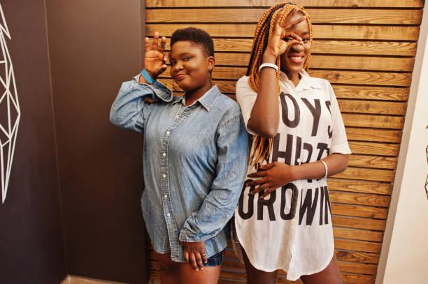 zwei afrikanische damen in stilvoller, lässiger kleidung posieren gegen die hölzerne wand und zeigen die finger. - damen hosen angels stock-fotos und bilder