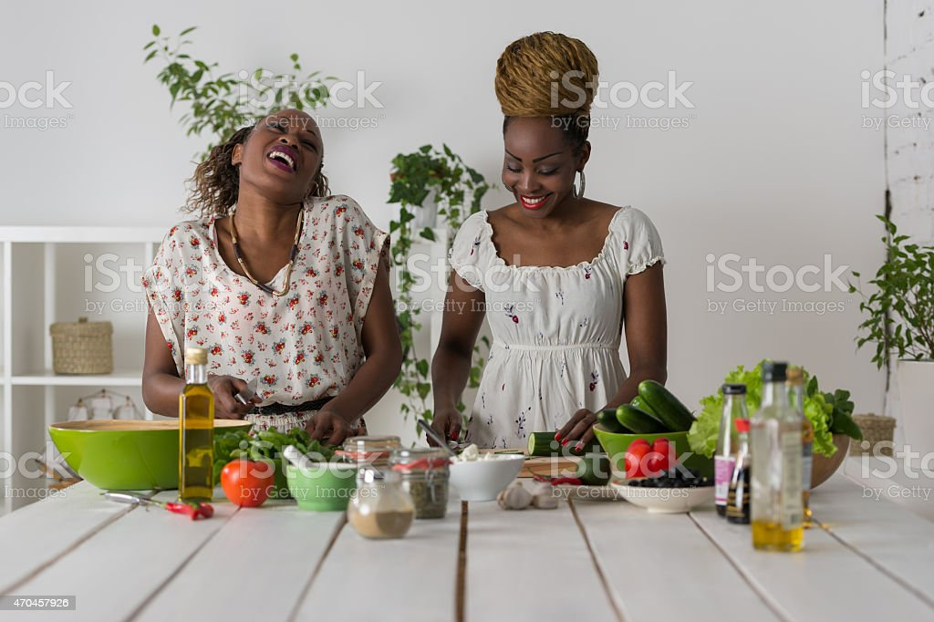Two african women cooking salad stock photo