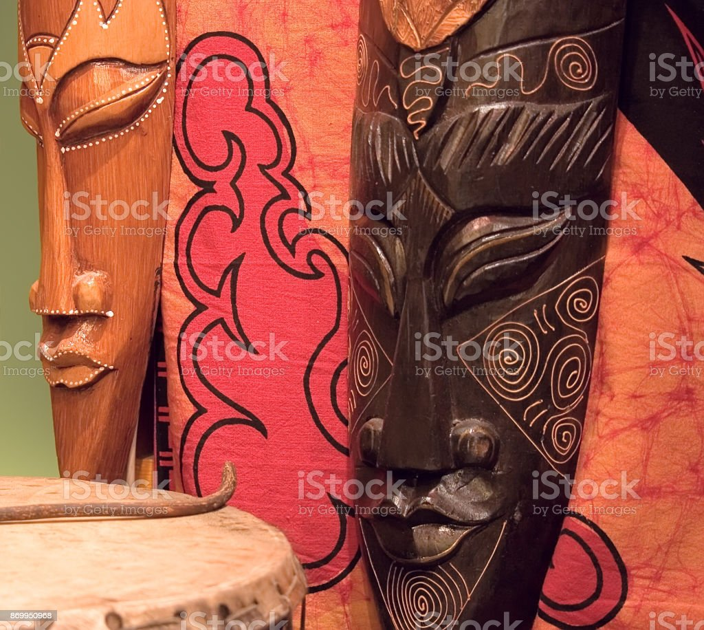 Two african wooden masks, tomtom and red painted fabric. stock photo