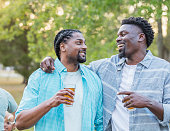 istock Two African-American men outdoors, drinking, talking 1091106020