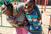 African-Americas preteen twin girls of elementary age active in playground at recess playing together. School in the background. Very sunny mid-season day. Horizontal waist up outdoors shot on a bright sunny day with copy space.