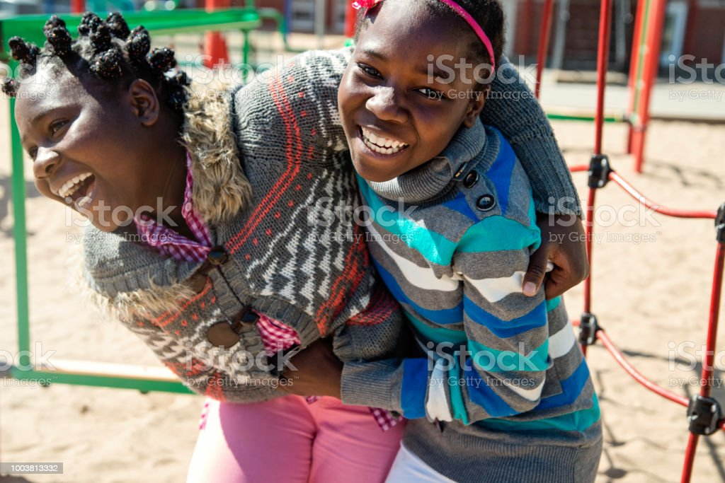 Two african-american twin girls playing in school playground at recess.. stock photo