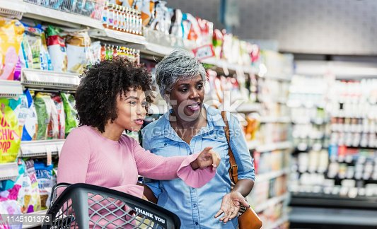 Two African-American women shopping together in a supermarket. The younger one, in her 20s, is carrying a shopping basket, smiling and pointing something out to the senior woman, in her 60s, who is standing beside her.