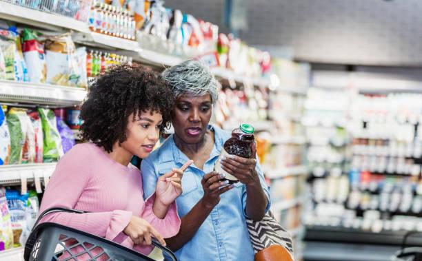 twee afro-amerikaanse vrouwen in de supermarkt - ingrediënt stockfoto's en -beelden