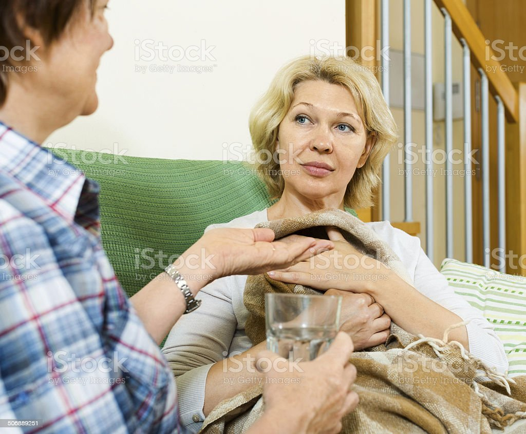 Two aged women with pill and glass of water stock photo