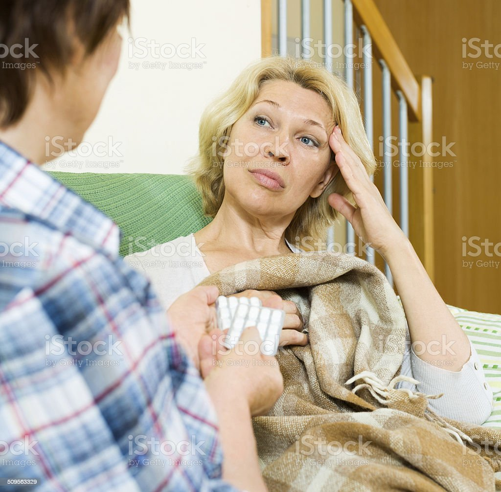 Two aged women with pill on couch stock photo