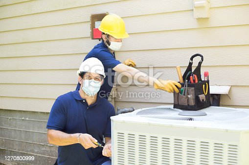 Latin and Caucasian air conditioner service workers work on the outdoor unit for a senior man. .  workers wear face masks due to COVID-19