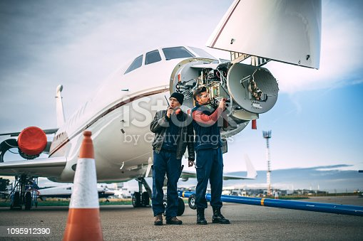 Two aircraft technicians working on a sensor array in the nose cone of a private airplane parked outside on a tarmac.