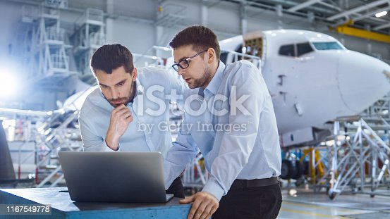 Two Aircraft Mechanics Working and Having Conversation next to Laptop Computer
