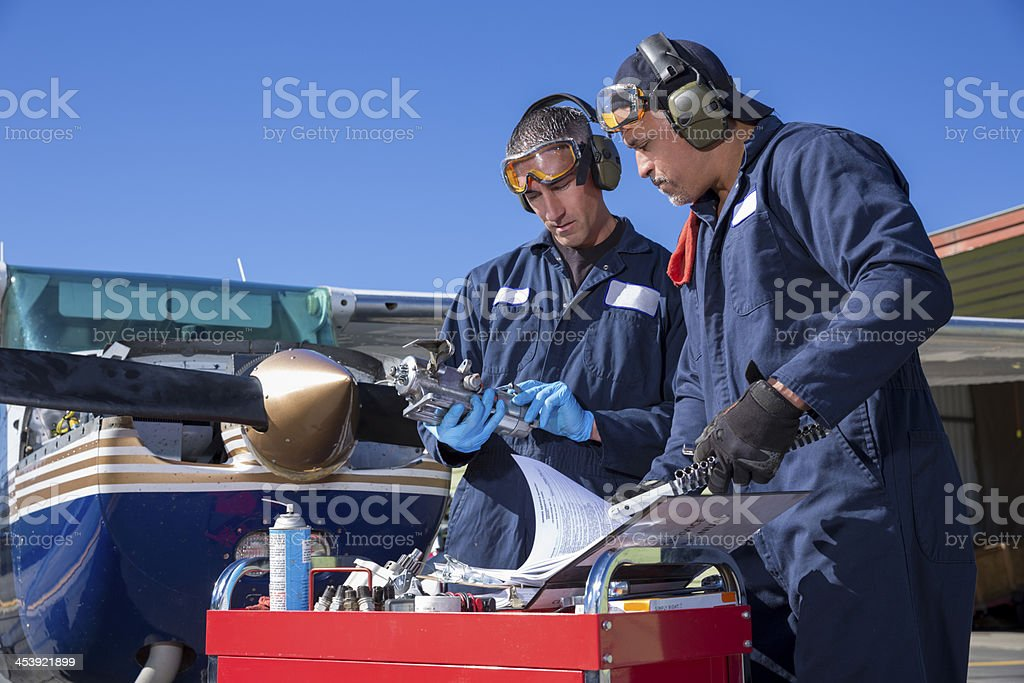 Two airplain mechanics working on a small plane stock photo