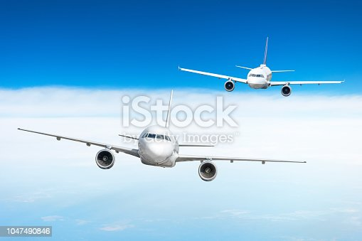 istock Two airplanes fly one by one over the clouds. 1047490846