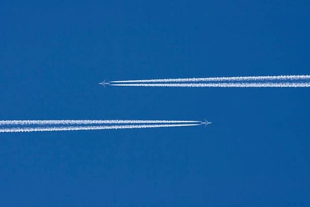 deux avions dans un ciel bleu avec trainée d'avion - imploser photos et images de collection