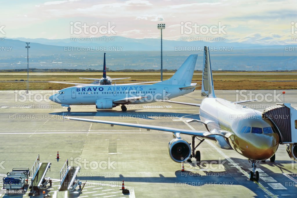 Two airplanes Qatar and Bravo airways at airport. To one there is an jetway. Civil aviation, passenger transportation. stock photo