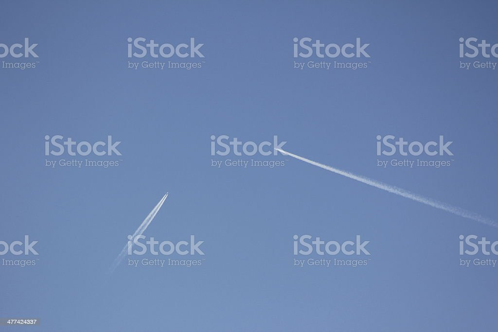 Two Airplanes with Vapor Trail in the Blue Clear Sky royalty-free stock photo