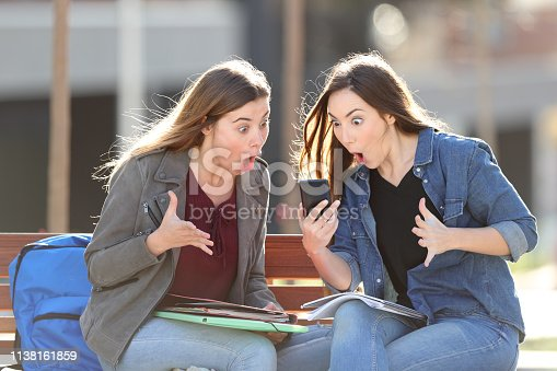 istock Two amazed students checking phone content in a park 1138161859