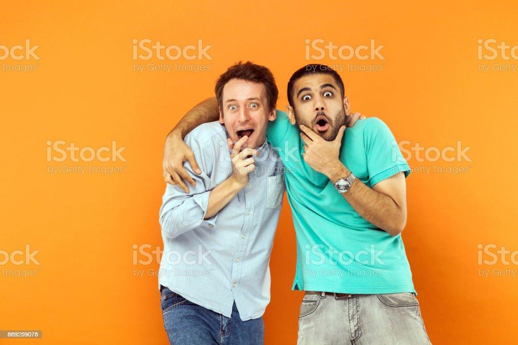 Zwei Freunde staunen umarmen, halten sein Kinn und Blick in die Kamera mit schockiert Gesicht. – Foto