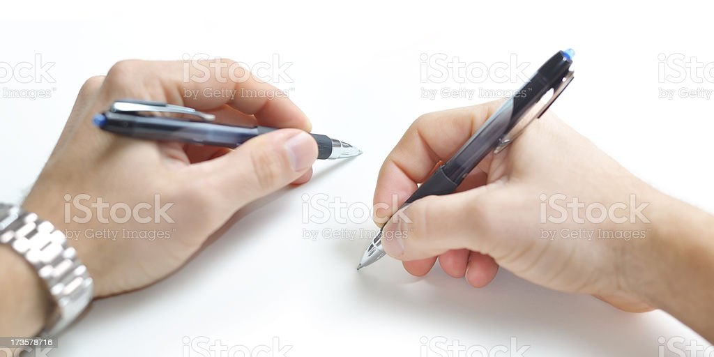 Two ambidextrious hands writing simultaneously. stock photo