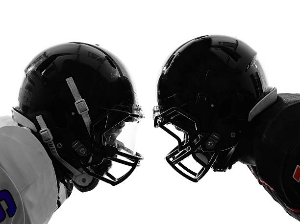 two american football players facing eachother silhouette two american football players face to face in silhouette shadow on white background face to face stock pictures, royalty-free photos & images