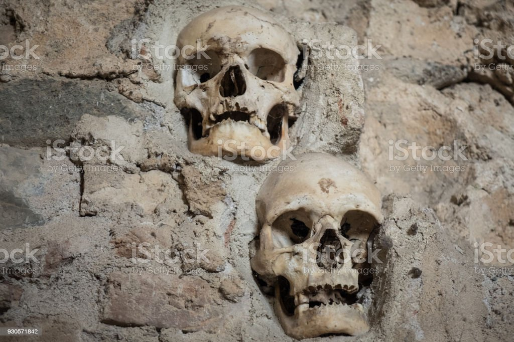Two ancient human sculls fixed in the stone wall stock photo