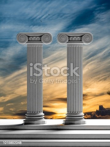 istock Two ancient pillars with sunset sky background. 1015852048